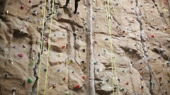 Back of woman downing with special equipment on climbing wall Stock Footage