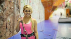 Smiling girl poses with safety rope in climbing gym center Stock Footage