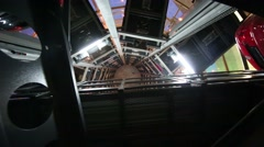 Bottom view of rising lift in tower to store cars at evening Stock Footage