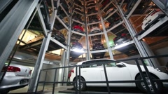 White car on lift and many other cars in tower to store Stock Footage