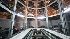 Empty lift and many new cars in tower to store cars Stock Footage