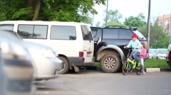 Happy brother and sister ride bicycle near car parking Stock Footage