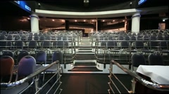 Stairs among rows of seats in empty illuminated auditorium Stock Footage