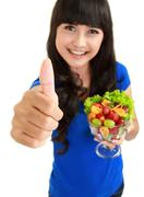 Stock Photo of portrait of a smiling woman with a bowl of fruit salad wishing you luck