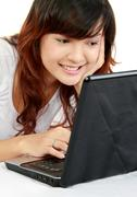 Stock Photo of woman with laptop on bed