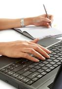 Stock Photo of woman write a book and typing her laptop