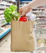 Hand holding a paper bag with groceries Stock Photos
