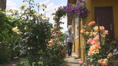 Man at home yard, walking on alley, relaxing, beautiful flowers ornament decor Stock Footage