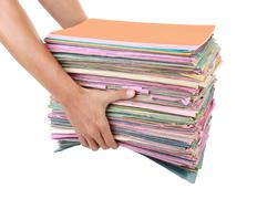 Stock Photo of man holding stack of folders pile with old documents and bills