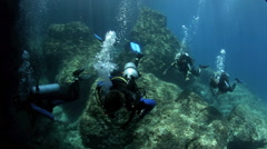 Scuba divers entering underwater tunnel Stock Footage