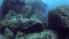 Scuba divers swimming amongst giant boulders Stock Footage