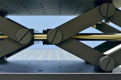 Fragment of lab jack mechanism on the steel table; used in opto-mechanics and Stock Photos