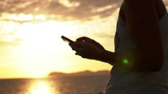 Stock Video Footage of Woman Using iPhone at Sunset in Slow Motion.