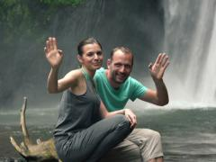 Young couple waving hand by beautiful waterfall In Bali NTSC Stock Footage