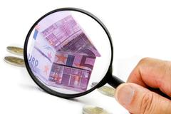 Euro bill house and expenses under magnifying glass Stock Photos