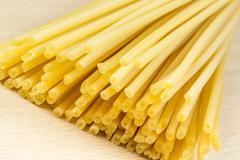 uncooked italian spaghetti on a white background - stock photo