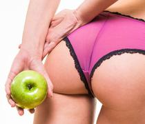 female with perfect buttocks and apple in hand - stock photo