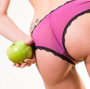 Sensual female with nice buttocks and apple in hand Kuvituskuvat