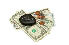 Charity stone with money over white Stock Photos