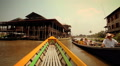 Boats go by a floating village at Inle Lake, Myanmar. Footage