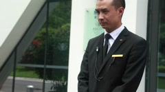 A doorman in china ready to open the car door Stock Footage
