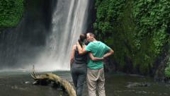 Couple in love admire amazing waterfall on Bali island HD Stock Footage