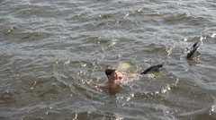 The young man swims with a Bicycle. 4K. Stock Footage