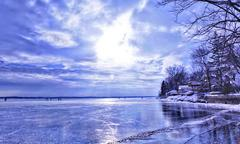 Frozen Lake - reflective ice, shoreline, dramatic sky - stock photo