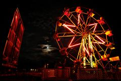 Ferris wheel and full moon at carnival Stock Photos