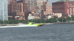 Fast tourist board East River past ship Manhattan Stock Footage