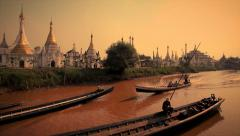 Long teak wood boats go by temple stupas at Inle Lake, Myanmar Stock Footage