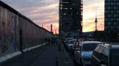 Pedestrians near berlin wall with iconic TV tower in background, Berlin Germa Stock Footage