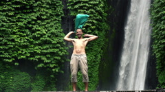 Crazy, excited funny man waving t-shirt by amazing waterfall HD Stock Footage