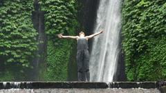Happy woman enjoying amazing waterfal in Bali, super slow motion, 240fps HD - stock footage