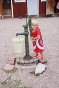 girl next to old waterpump - stock photo
