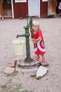 Girl next to old waterpump Stock Photos