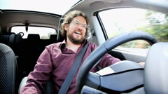 Happy man driving car listening to joke of a friend with speakerphone Stock Footage