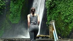 Woman walk, admire beautiful waterfall in Bali, super slow motion, 240fps HD - stock footage
