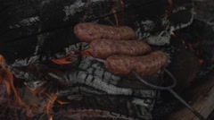Sausages cooking on an open fire - slow motion 300fps - stock footage