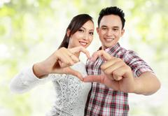 Stock Photo of young couple showing heart with fingers