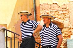 two gondolier on the docks awaiting tourists in venice, italy - stock photo