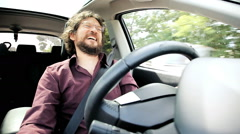 Man laughing while driving car talking on speakerphone Stock Footage