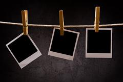 Photography paper with instant photo frames attached to rope with Stock Photos