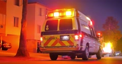 Flashing lights of ambulance van illuminating street of night city neighborhood - stock footage