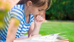 Stock Video Footage of Little girl reading a book in summer on grass.Girl Reading.Dolly shot