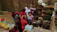 Women in Nepal fill their water vessels. - stock footage