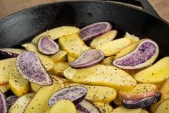 Blue and yellow potatoes in a skillet Stock Photos