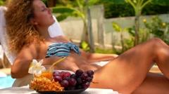 Beautiful Natural Woman Eating Fresh Fruits near Swimming Pool. Stock Footage