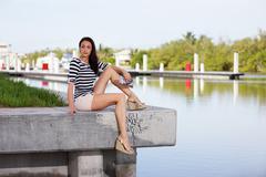 Woman sitting on a concrete ledge Stock Photos