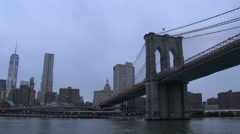 Brooklyn bridge and Freedom tower at night from the East river , New York City Stock Footage